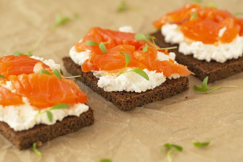 K?senahaufnahme des Sandwiches des ger?ucherten Lachses mit Sahne Geschmackvoller Imbi? stockfoto