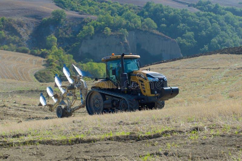 2K11 siguió el desafiador MT775E del tractor con una paleta en las colinas de Toscana en un día soleado del otoño imágenes de archivo libres de regalías