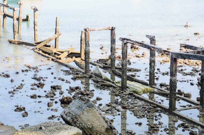 K?stenlandschaft mit altem gebrochenem Pier stockfotos