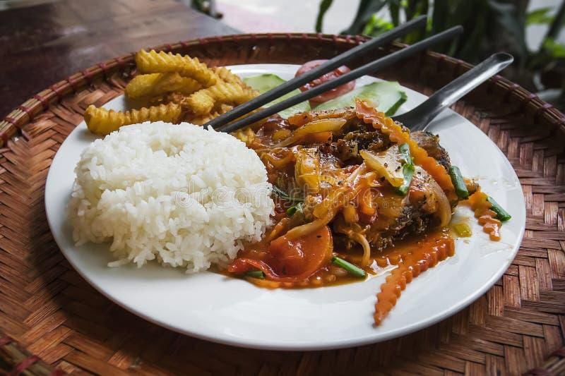 K?stliche K?che Eine Platte des gekochten Reises mit gebratenen Meeresfrüchten mit Gemüse auf einer Tabelle in einem Straßenresta stockfotografie