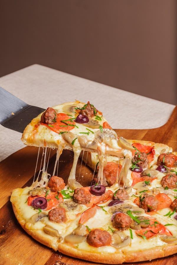 K?stliche Pizza diente auf h?lzerner Platte - Imagen lizenzfreie stockfotografie
