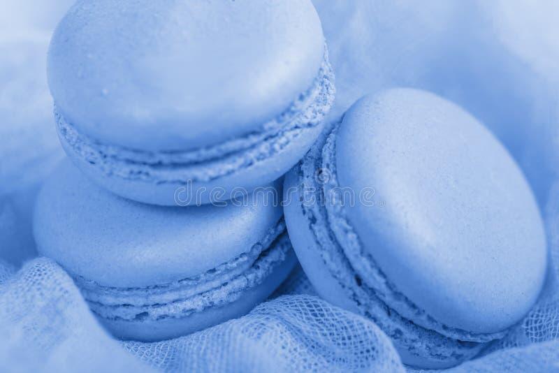 K?stlicher franz?sischer Nachtisch Pastellmacaron oder Makrone mit drei leichtes weiches blaues Kuchen auf luftigem Gewebe lizenzfreie stockfotos