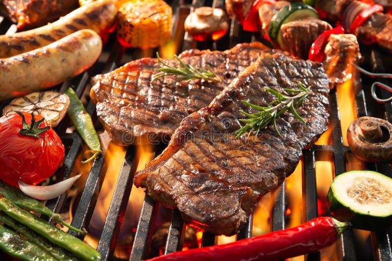 K?stliches gegrilltes Fleisch mit dem Gem?se, das ?ber den Kohlen auf Grill zischt lizenzfreie stockbilder
