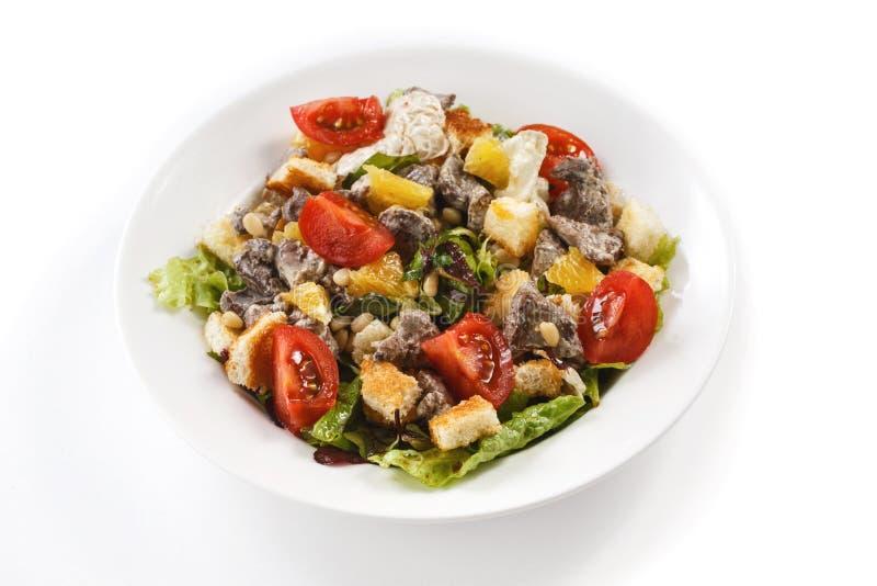 K?ttsallad med havre, sm?llare, ?rter och tomater i en platta p? en isolerad vit bakgrund royaltyfria foton