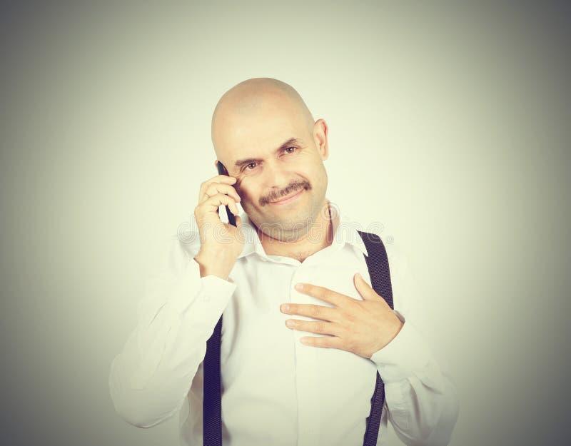 Kaal mustachioed de mens die op de telefoon spreken stock foto's