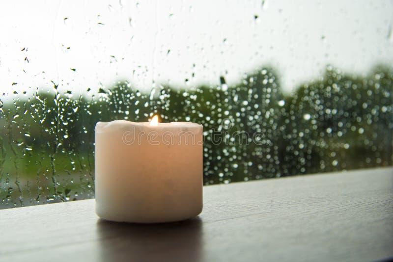 Kaars door de vensterregen stock foto