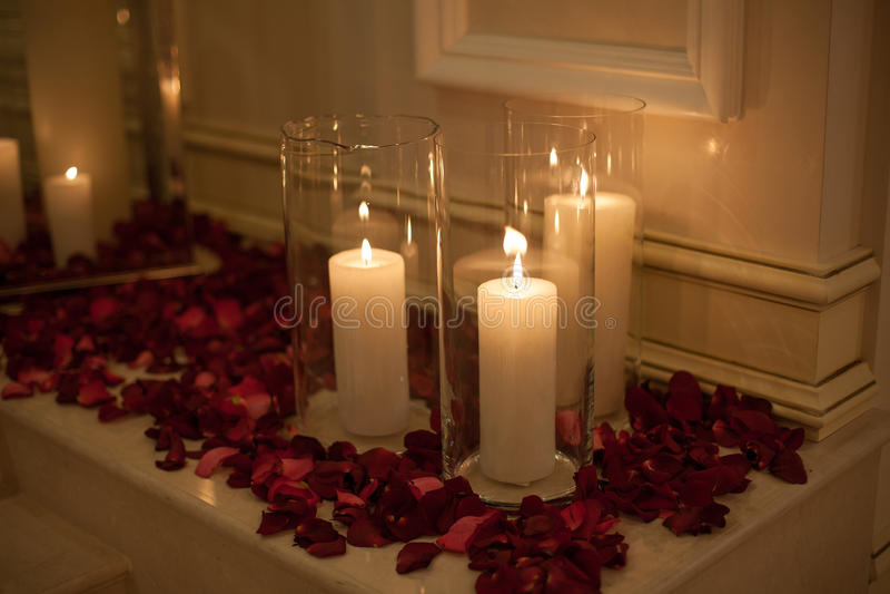 Kaars door rode roze bloemblaadjes met dromerige bezinning wordt omringd die royalty-vrije stock afbeeldingen