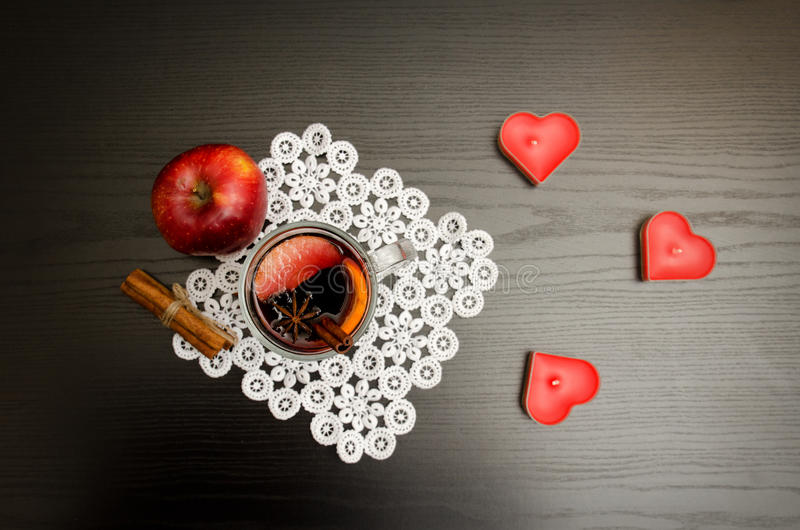 Kaarsen in de vorm van een hart, een overwogen wijn met kruiden op een kantservet, een appel en pijpjes kaneel Zwarte houten acht stock foto's