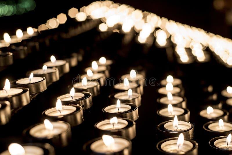 Kaarsen die voor geestelijk dienstenaanbod in een heiligdom onder de berg worden aangestoken stock foto