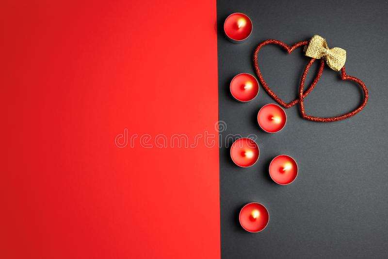 Kaarsen en decoratieve harten op een rood-grijze achtergrond royalty-vrije stock afbeeldingen