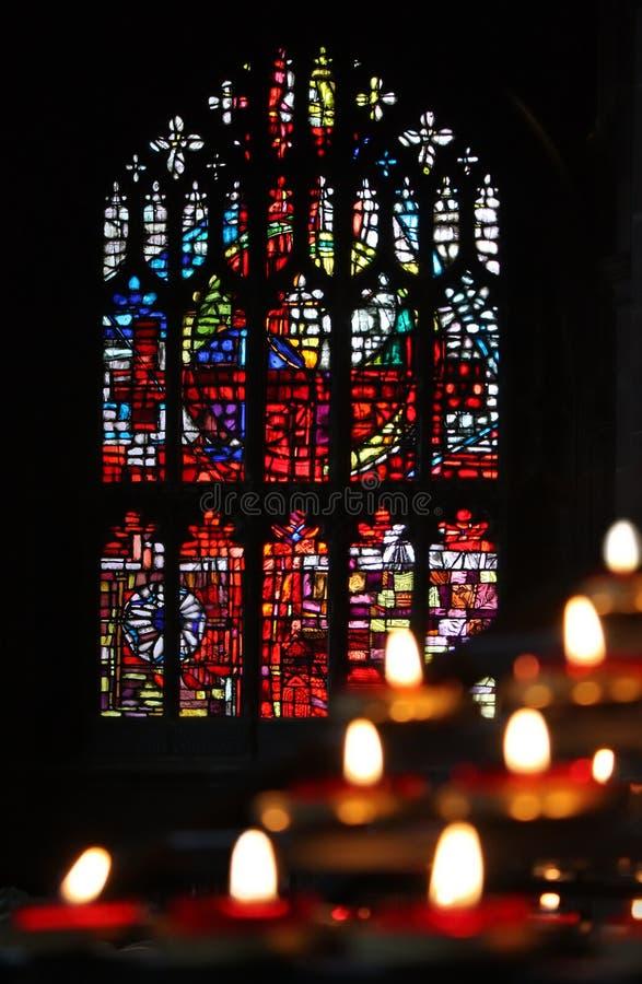 Kaarsen en gebrandschilderd glas in de kerk royalty-vrije stock afbeelding