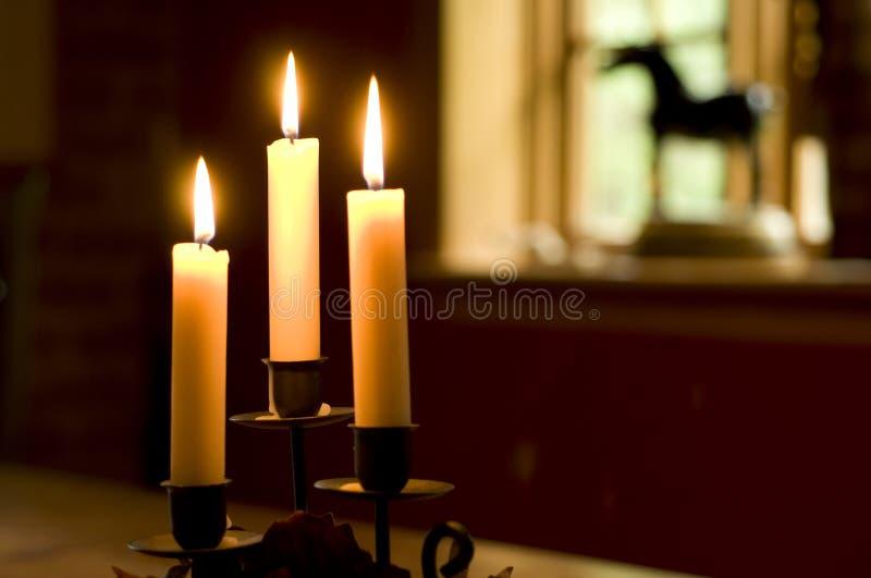 Kaarsen en venster stock foto