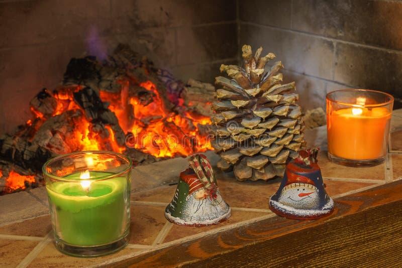 Kaarsen, Kerstmisklokken, en denneappels dichtbij open haard stock fotografie
