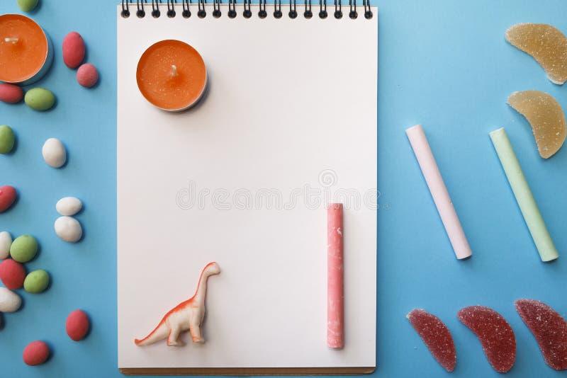 Kaarsen, kleurpotloden, pinda's in gekleurde glans, notitieboekje voor stock afbeelding