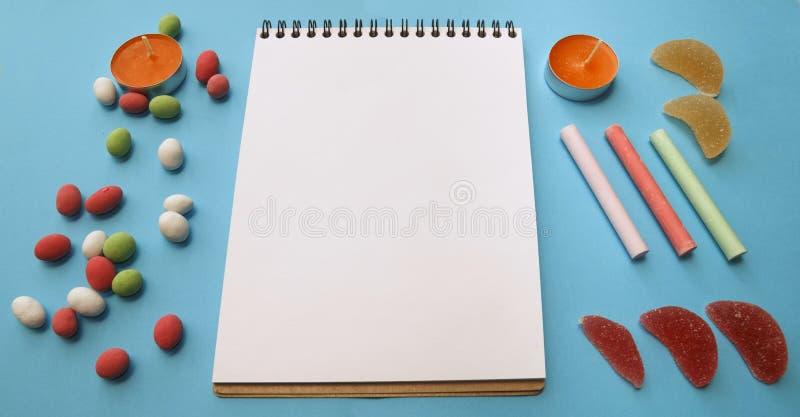 Kaarsen, kleurpotloden, pinda's in gekleurde glans, notitieboekje voor stock foto's