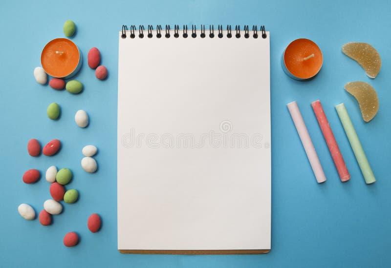 Kaarsen, kleurpotloden, pinda's in gekleurde glans, notitieboekje voor royalty-vrije stock foto