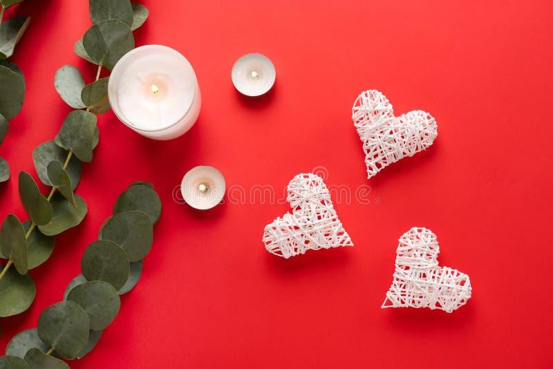 Kaarsen met eucalyptustakken en harten op kleurenachtergrond royalty-vrije stock foto