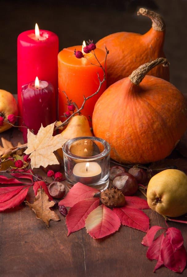 Kaarsen, pompoenen en de herfstbladeren stock fotografie