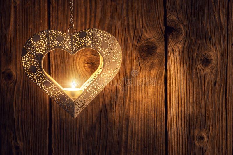 Kaarshouder met kantontwerp met thee binnen kaars, kaarshouder op houten achtergrond, romantische achtergrond voor valentijnskaar stock afbeelding