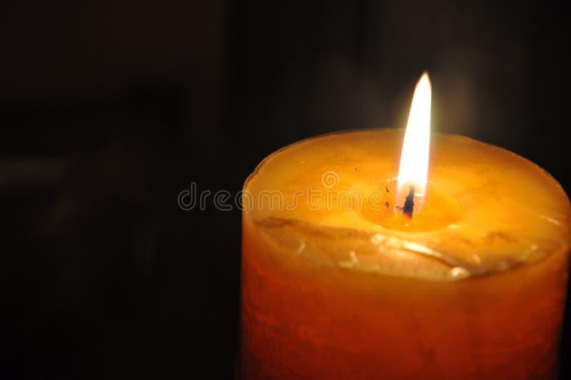 Kaarslicht de donkere nacht Het gele, oranje kaars branden, gele vlammen en donkere, zwarte achtergrond royalty-vrije stock afbeeldingen