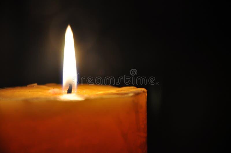 Kaarslicht de donkere nacht Het gele, oranje kaars branden, gele vlammen en donkere, zwarte achtergrond stock afbeeldingen