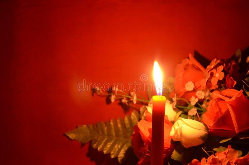 Kaarslicht en rozen op rode achtergrond royalty-vrije stock afbeeldingen