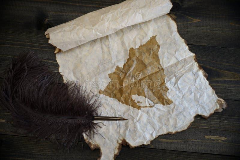 Kaart van Nicaragua op uitstekend document met oude pen op het houten textuurbureau stock foto's