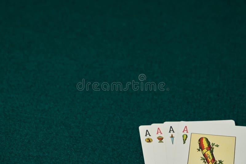 Kaarten van de vier azen van het Spaanse dek op een groene spelmat Met de vier triomfen: gouden medailles, koppen, zwaarden en st stock foto's