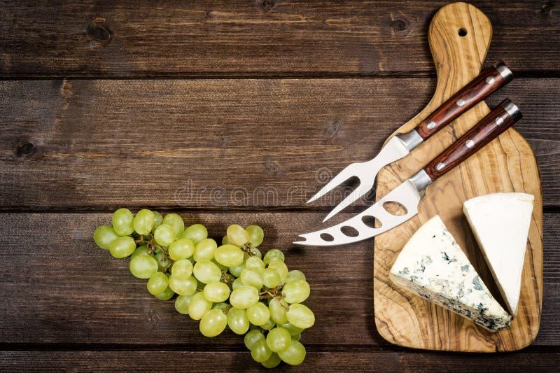 Kaas, druiven, mes en vork stock afbeeldingen