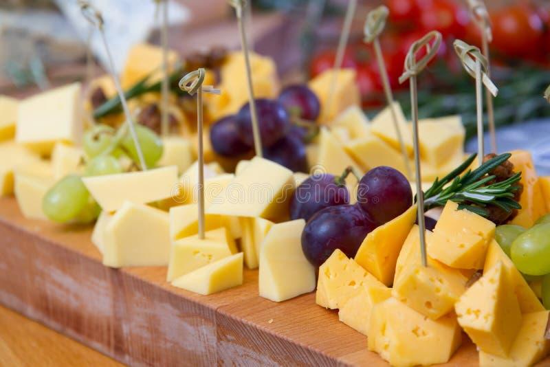 Kaas en druif op de houten raad stock afbeeldingen