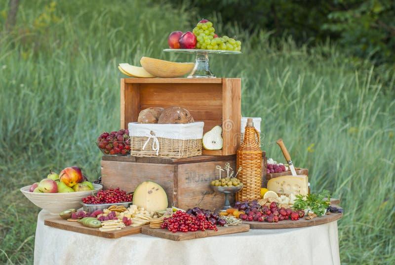 Kaas en vruchten op een prachtig wijnoogst verfraaide lijst stock afbeeldingen