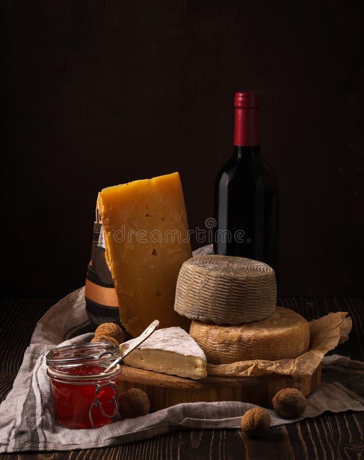 Kaas, jam en wijn op het ruwe hout stock foto