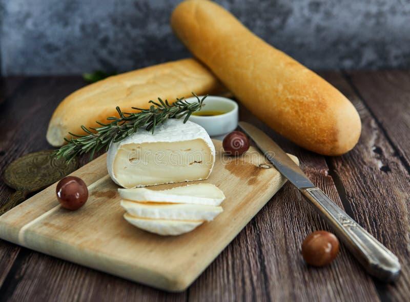 Kaas op een houten lijst met olijven en brood stock fotografie