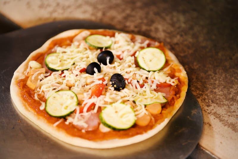 Kaas op een vers voorbereide pizza op houten raad stock fotografie