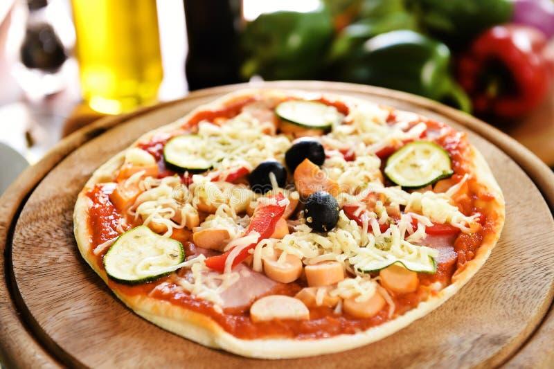Kaas op een vers voorbereide pizza op houten raad royalty-vrije stock afbeeldingen