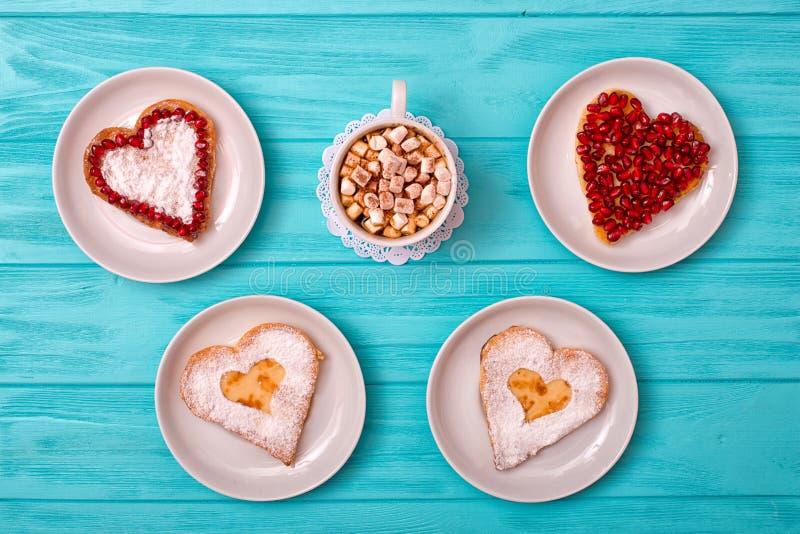 Kaaspannekoeken in de vorm van een hart en een kop van koffie met heemst Romantisch ontbijt stock foto's