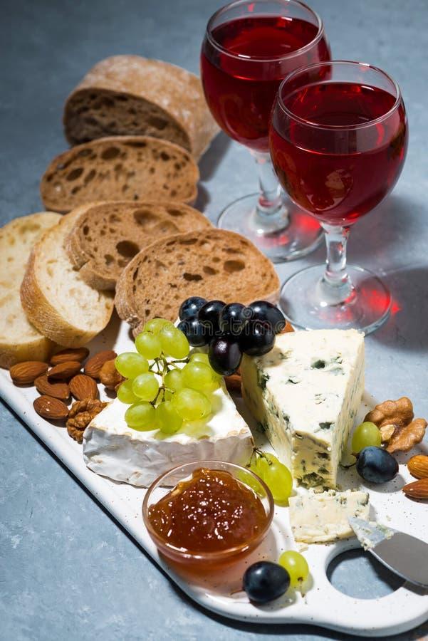 Kaasplaat, ciabatta, verse druiven en twee glazen rode wijn royalty-vrije stock afbeelding
