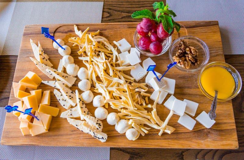 Kaasplaat in het restaurant Verschillende verscheidenheden van kaas op een houten dienblad Honing, druiven en okkernoten royalty-vrije stock fotografie