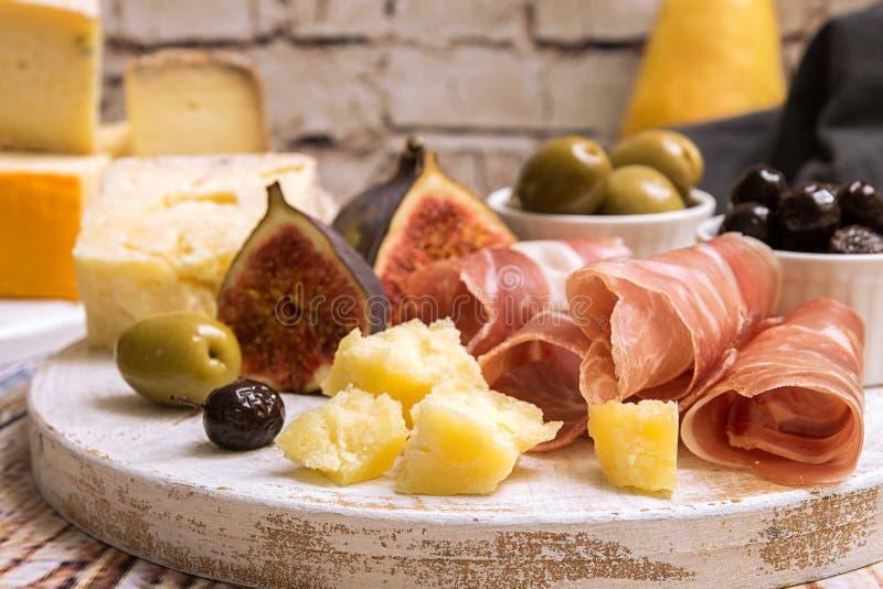 Kaasplaat met Plakken van prosciutto, stukken van kaas, olijven stock afbeeldingen
