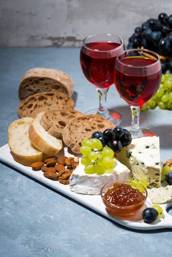 kaasplaat, verse ciabatta, druiven en twee glazen rode wijn royalty-vrije stock afbeeldingen