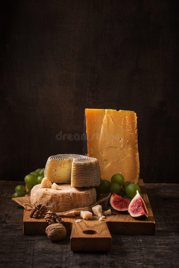 Kaasraad, vruchten en noten op het ruwe hout royalty-vrije stock afbeelding