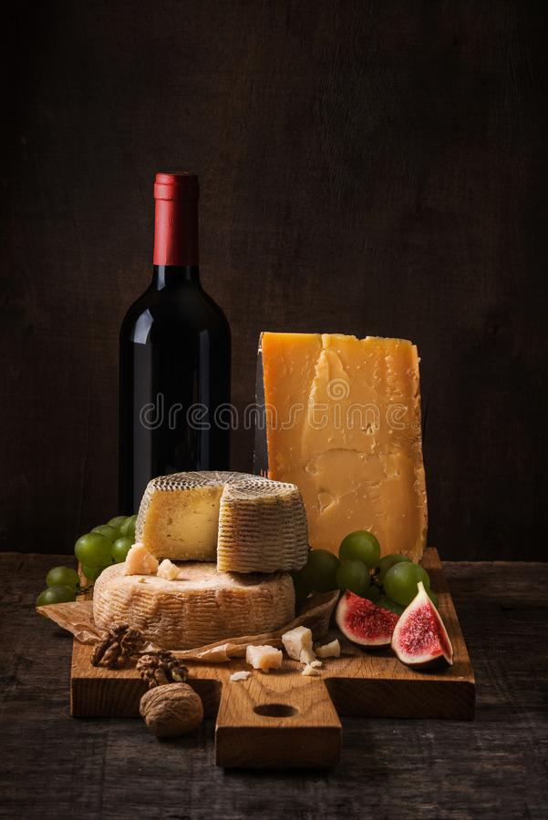 Kaasraad, vruchten en wijn op het ruwe hout royalty-vrije stock fotografie