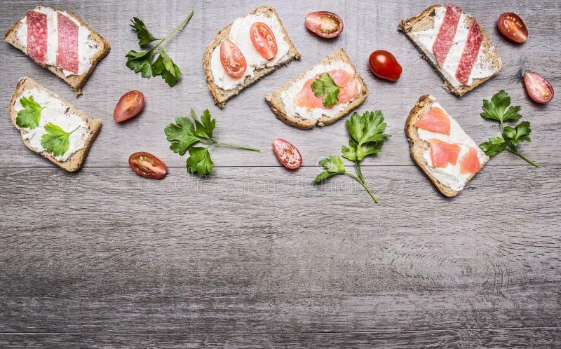 Kaassandwiches met tomaten op een tak en van de kruidenkers tomaten en zalm op houten rustieke achtergrond hoogste meningsgrens,  stock afbeelding