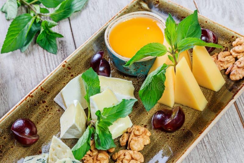 Kaasschotel met honing, okkernoten, druiven, brood, munt en glas wijn over houten achtergrond wordt versierd die stock afbeelding