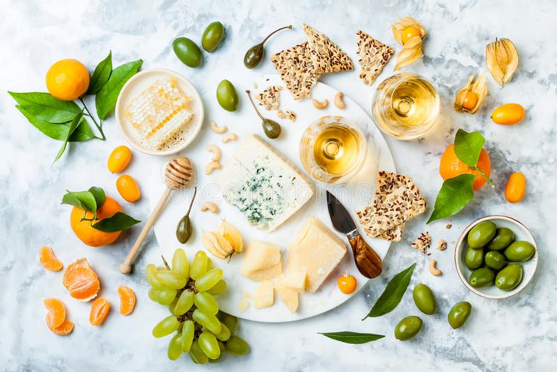 Kaasschotel met verschillende kazen, druiven, noten, honing Voorgerechtenlijst met antipastisnacks De raad van de kaasverscheiden royalty-vrije stock afbeeldingen
