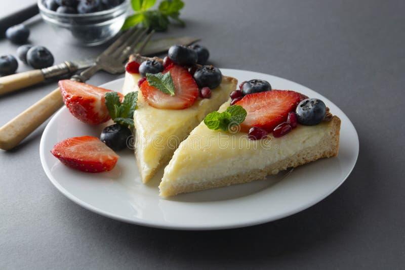 Kaastaartenplakken in grijze plaat, met verse bessen en munt voor dessert - gezonde organische de pasteikaastaart van het de zome royalty-vrije stock fotografie