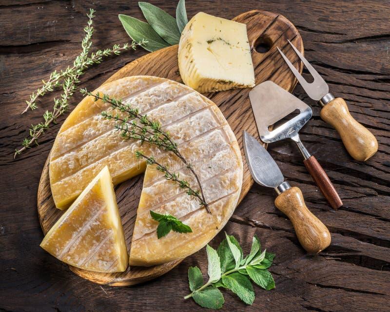Kaaswiel met kruiden en bestek op de houten achtergrond stock afbeelding
