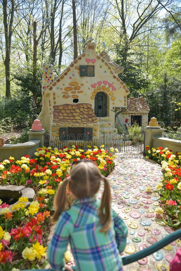 KAATSHEUVEL, NETHERLANDS - APRIL 19, 2019: Girl looks at the house of the Little Red Riding Hood in Efteling Park in the Holland royalty free stock photos