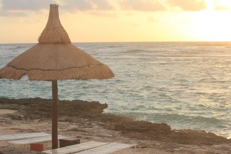 Kabanna på en strand mot havet och en guling, orange soluppgång royaltyfria foton