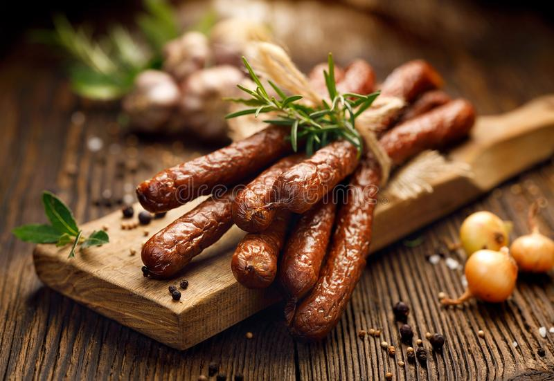 Sausages on a wooden rustic table with addition of fresh aromatic herbs and spices, natural product from organic farm, produced b. Kabanosy, polish sausages made stock photography